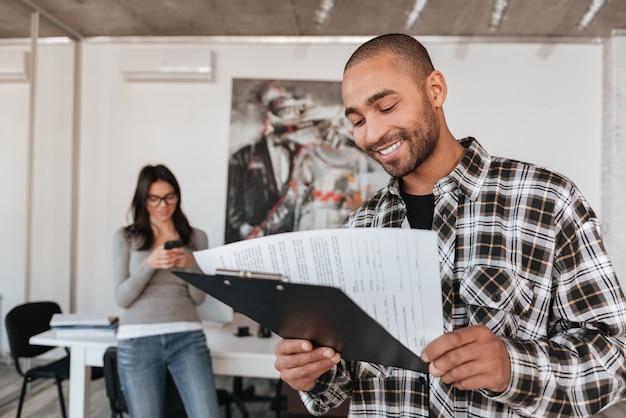 屋内で幸せな若いビジネスパートナーの画像。クリップボードを保持しているアフリカ人。人に焦点を当てます。