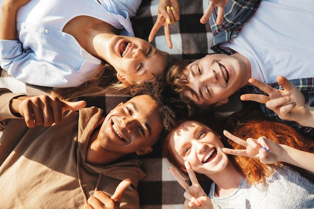 행복한 젊은 친구 남성과 여성의 웃음과 원 안에 담요에 누워있는 이미지