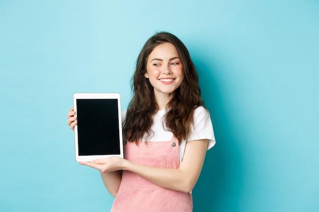 디지털 태블릿 화면을 보여주고 자랑스럽게 웃고 있는 행복한 어린 소녀의 이미지, 파란색 배경 위에 서 있는 디스플레이에 귀하의 로고를 보여줍니다.