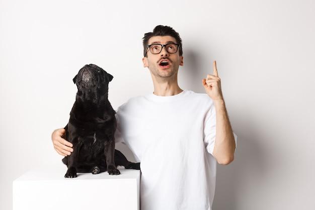 Изображение счастливого молодого человека и собаки, смотрящих вверх на промо, владельца, указывающего пальцем вверх, мопса, смотрящего на луг, стоящего на белом фоне