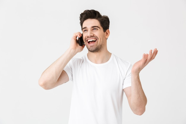 携帯電話で話している白い壁の上に孤立してポーズをとって幸せな若い男の画像。