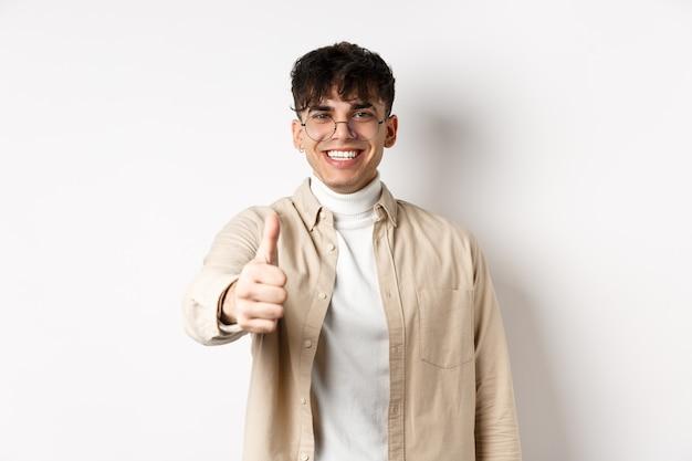 Изображение счастливого молодого человека показывает палец вверх и удовлетворенно улыбается, хвалит хорошую работу, говорит, что хорошо сделано и выглядит довольным, стоя на белой стене.