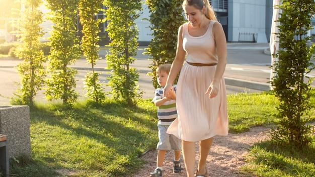 3살 된 어린 아들이 공원의 어린이 놀이터에서 놀고 달리는 행복한 젊은 어머니의 이미지