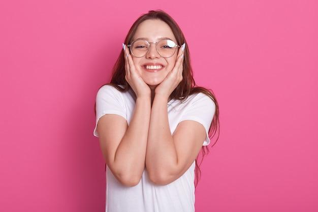 Изображение счастливой молодой женщины, наполненной надеждой и позитивным отношением, смотрит на камеру с радостной улыбкой и держит руки на щеках, позируя поверх розового, одетого повседневного наряда и очков.