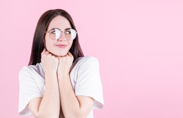 Изображение счастливой молодой женщины, позирующей изолированно на розовом фоне, смотрящей на copyspace в правом углу