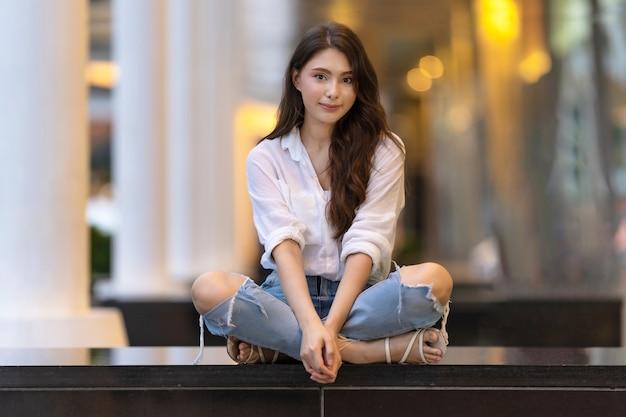 Изображение счастливой молодой женщины, сидящей на полу ночью в городе