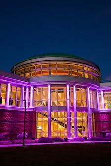 夕暮れ時に多くの窓が紫色に点灯しているモダンな建物の正面玄関のショットの頭の画像
