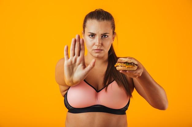 Изображение здоровой пухлой женщины в спортивном костюме, делающей стоп-жест, держа сэндвич, изолированное на желтом фоне