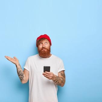 Изображение нерешительного рыжеволосого парня позирует со своим телефоном