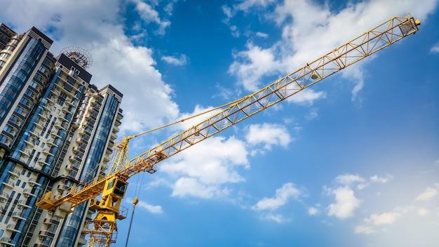 Изображение высокого строительного крана на строительной площадке против голубого неба и небоскребов