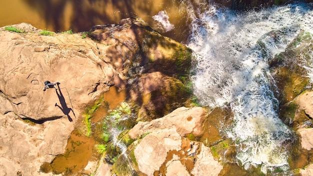 カスケードする白い滝の横にある茶色の岩の上に人物の長い影がある上からのハイカーの画像