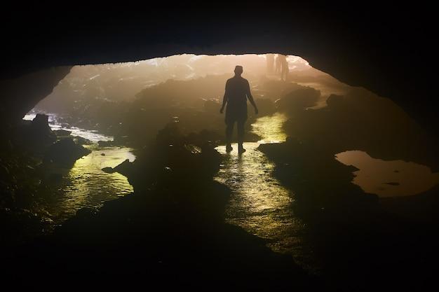 Изображение человеческого силуэта, стоящего в отверстии пещеры