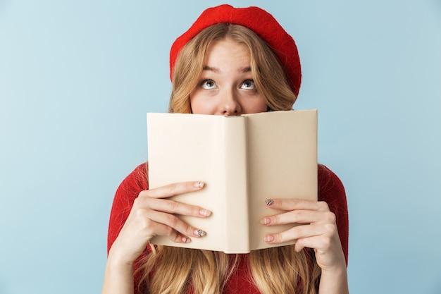 Изображение скромной белокурой женщины 20-х годов в красном берете, читающей книгу изолированы