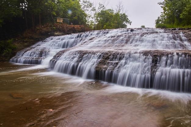 緑の森の傾斜した岩の上に流れ落ちる何百もの滝の画像