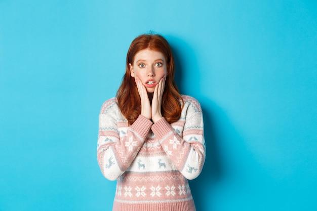 感動した赤毛の女の子が息を切らしてカメラを見つめている画像は、青い背景に冬のセーターに立って、大きなニュースを聞きます。