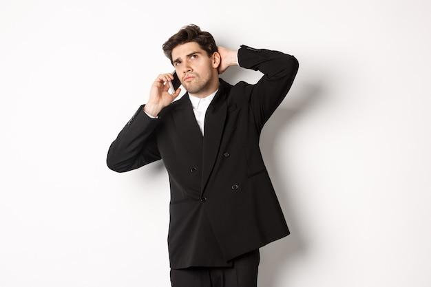 電話で話し、考え、疑わしい顔をして、決定を下し、白い背景の上に立っている優柔不断なビジネスマンの画像