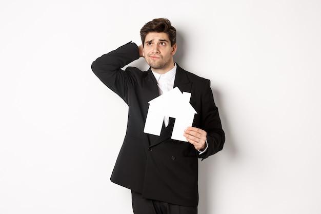 白い背景に立って、考え、家のmaketを保持し、左上隅を疑わしい見ている優柔不断なビジネスマンの画像