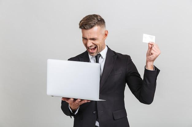ノートパソコンとクレジットカードを分離して保持しながら驚くべきフォーマルなスーツを着た楽しい大人のビジネスマンの画像