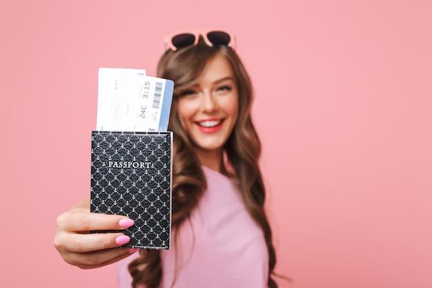 Изображение радостной красивой женщины в повседневной одежде, показывающей паспорт и авиабилеты на камеру, изолированное на розовом фоне
