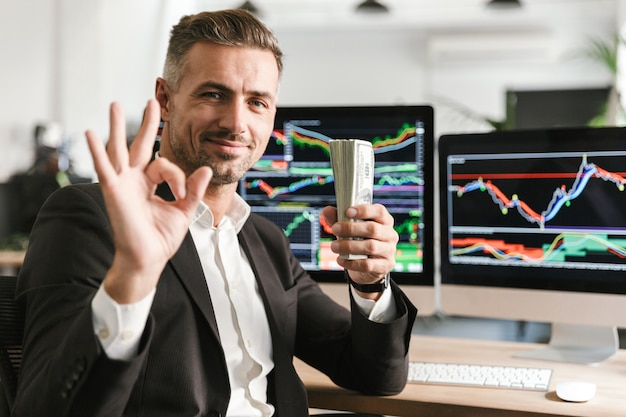 Изображение радостного бизнесмена 30-х годов в костюме, держащего пачку денег во время работы в офисе с графикой и диаграммами на компьютере