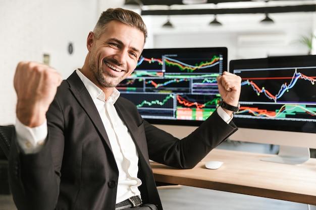 Изображение радостного бизнесмена 30-х годов в костюме, работающего в офисе на компьютере с графикой и диаграммами на экране