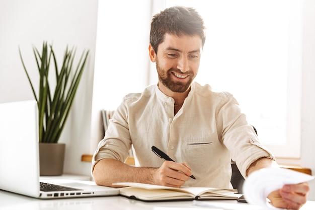 Изображение радостного бизнесмена 30-х годов в белой рубашке, работающего с ноутбуком и бумажными документами, сидя в ярком офисе