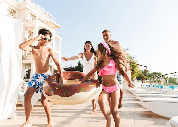 Изображение веселой кавказской семьи с детьми, отдыхающими возле роскошного бассейна и веселыми с резиновым кольцом возле отеля