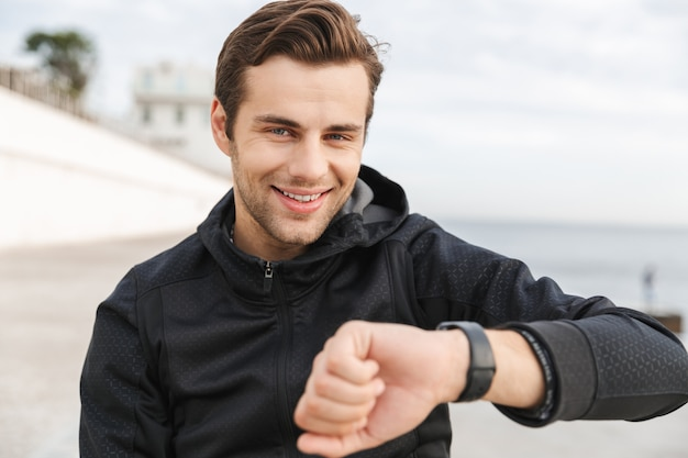 해변에서 산책로에 앉아있는 동안 손목 시계를보고있는 검은 색 운동복을 입은 즐거운 30 대 남성의 이미지