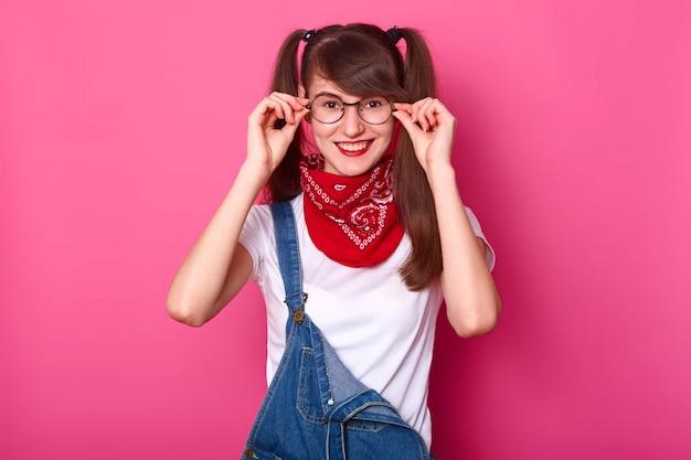 즐거운 십 대 소녀의 이미지 라운드 안경을 착용, 양성을 표현, 젊은이들을위한 유행 옷을 입고, 분홍색 wallpeople 및 행복 개념에 고립 된 그녀의 안경에 손을 유지합니다.