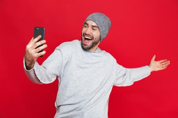 수염과 콧수염이 서있는 동안 스마트 폰을 들고 즐거운 남자 30 대의 이미지, 절연