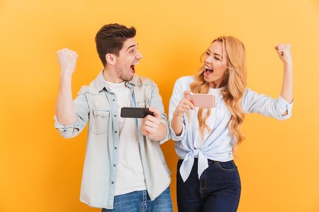 携帯電話で一緒にビデオゲームをプレイしながら喜びの男性と女性が拳を握り締めて喜んでいる画像
