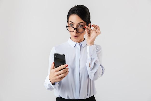 흰 벽 위에 절연 사무실에서 스마트 폰을 사용하여 안경을 쓰고 즐거운 비서 여자의 이미지