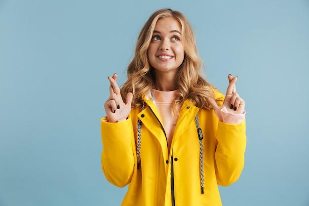 손가락을 유지하는 노란 우비를 입고 즐거운 여성 20 대의 이미지가 교차
