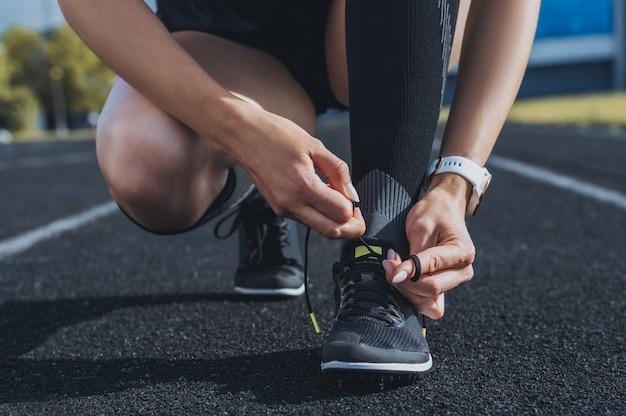 スタジアムのトラックで運動靴をひもで締める画像。ランニングコンセプト。