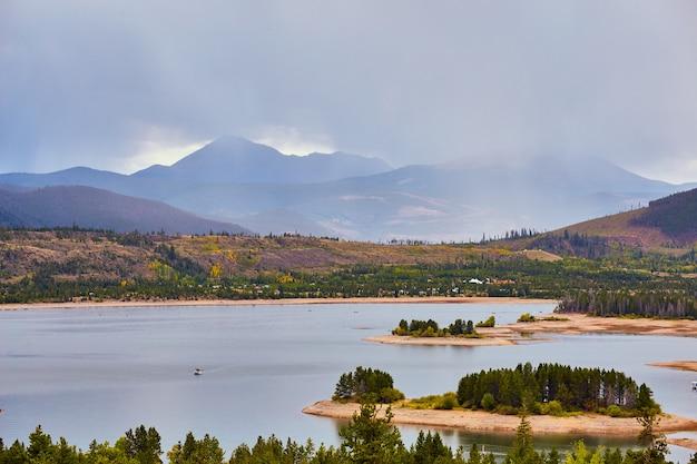 Изображение озера с небольшими островами и горами на заднем плане с проливным дождем