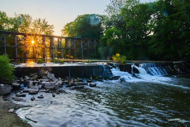 Изображение ландшафта открытой реки на закате или восходе солнца с искусственной плотиной, водопадами и железнодорожным мостом