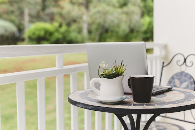 Изображение ноутбука с чашкой кофе и растения на столе на балконе с видом на сад.