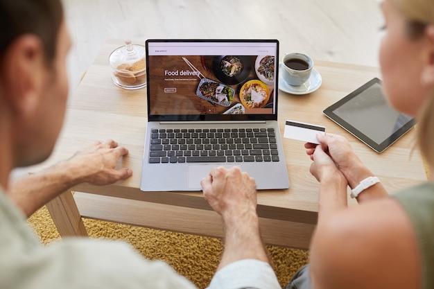 若いカップルが注文の支払いをしている画面上の食品配達サイトを備えたラップトップの画像