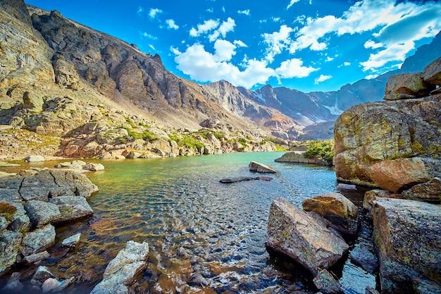 Изображение большого озера высоко в горах с валунами лишайника