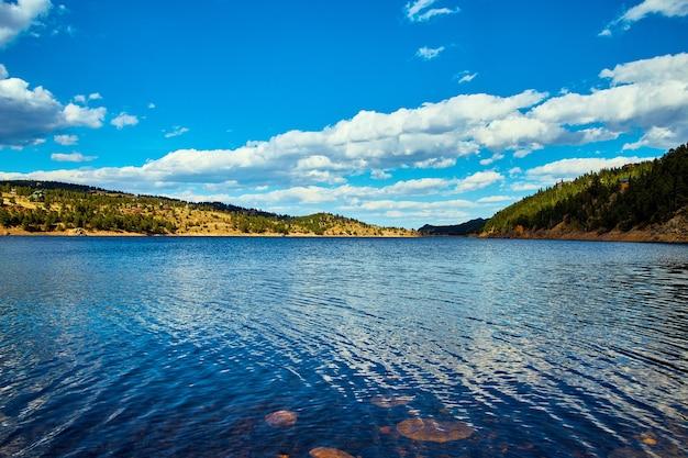Изображение большого озера в горном пейзаже с голубым небом