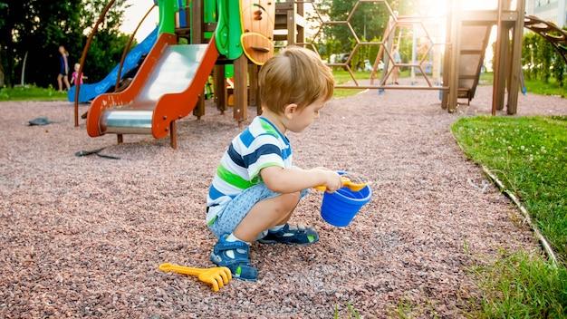Изображение маленького мальчика, сидящего на детской площадке и очищающего песок маленькой пластиковой лопатой в красочном ведре. малыш копает и строит в парке