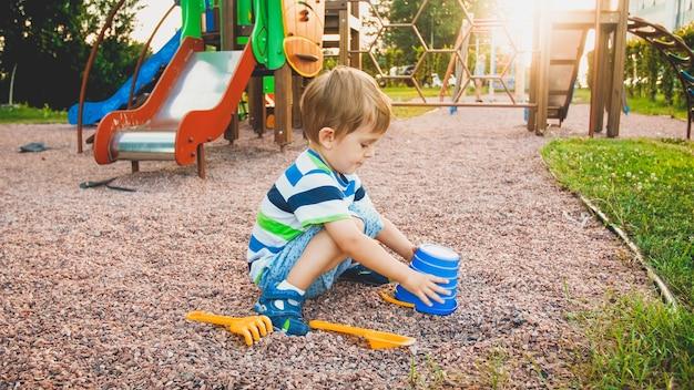놀이터에 앉아서 다채로운 양동이에 작은 플라스틱 삽으로 모래를 청소하는 어린 소년의 이미지. 공원에서 땅을 파고 건물을 짓는 아이