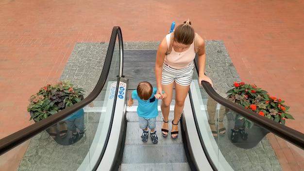 쇼핑몰이나 공항 터미널에서 에스컬레이터에 서 있는 동안 어머니의 손을 잡고 있는 어린 소년의 이미지