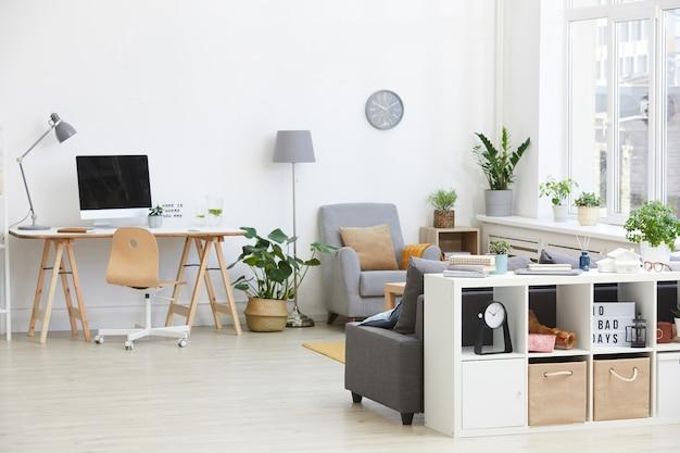 家の中にコンピューターとアームチェアを備えた職場のあるリビングルームの画像