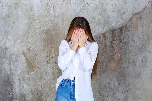 大理石の上に顔を覆っている長髪の少女の画像
