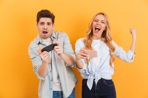 敗者の男と勝者の女性が一緒に遊んでいて、スマートフォンのビデオゲームで競合している画像