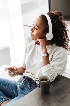 明るいキッチンに座って、スマートフォンを使用してヘッドフォンを身に着けている素敵なアフリカ系アメリカ人の女の子の画像