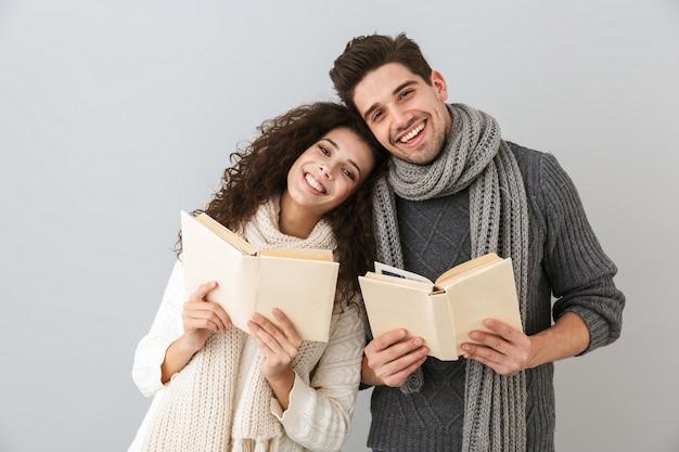 灰色の壁に隔離された、一緒に本を読んでいる素敵なカップルの男性と女性の画像