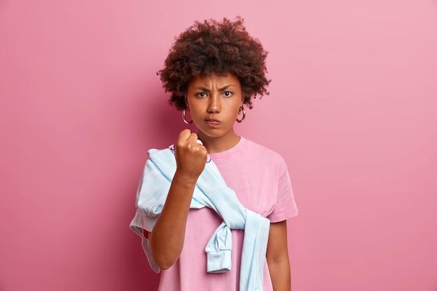 怒った憤慨した女性の画像は、拳を振って誰かを脅し、しかめっ面を憤慨させて警告します、ピンクの壁に隔離されたカジュアルな服を着てあなたに見せますと言います。否定的な感情