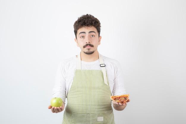 흰색에 피자와 녹색 사과를 들고 있는 남성 요리사의 이미지